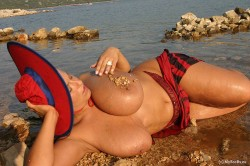 Aneta Buena in wet clothing posing in sea laying pebbles on her big natural tits