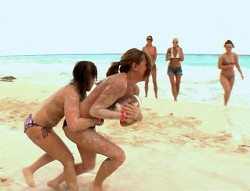 2 sexy girls covered with sand playing touch football at the beach